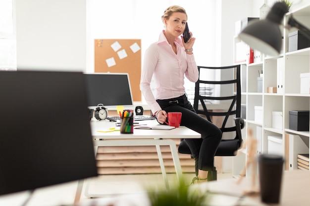 Une jeune fille blonde est assise sur une table dans le bureau, tient une tasse rouge dans sa main et son téléphone.