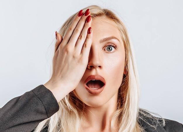 La jeune fille blonde est surprise couvre mal la moitié de son visage avec sa main sur fond blanc isolé