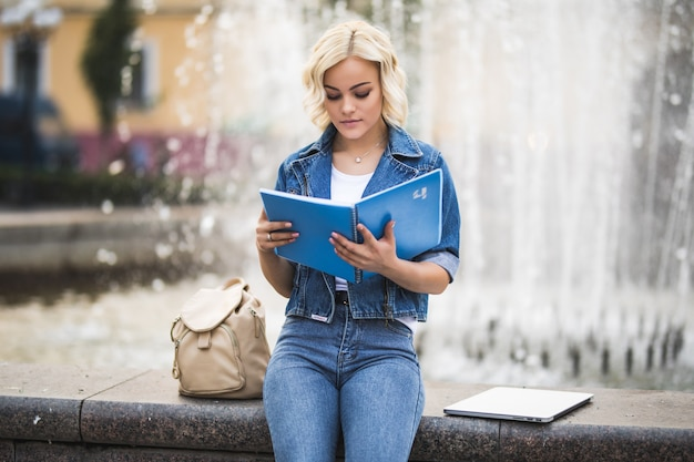 Jeune fille blonde étudiante travaille sur son ordinateur portable et lit un livre près de la fontaine dans la ville dans la journée