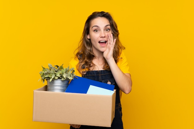 Jeune fille blonde faisant un geste tout en ramassant une boîte pleine de choses en criant avec la bouche grande ouverte
