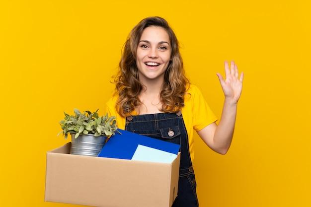 Jeune fille blonde faisant un geste tout en ramassant une boîte pleine de choses saluant avec la main avec une expression heureuse