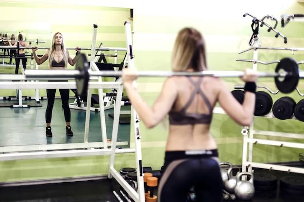 Jeune fille blonde fait des exercices avec haltères dans un gym.