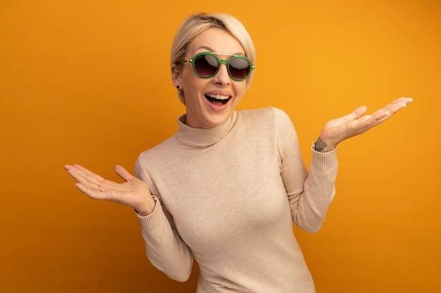 Jeune fille blonde impressionnée portant des lunettes de soleil montrant des mains vides isolées sur un mur orange