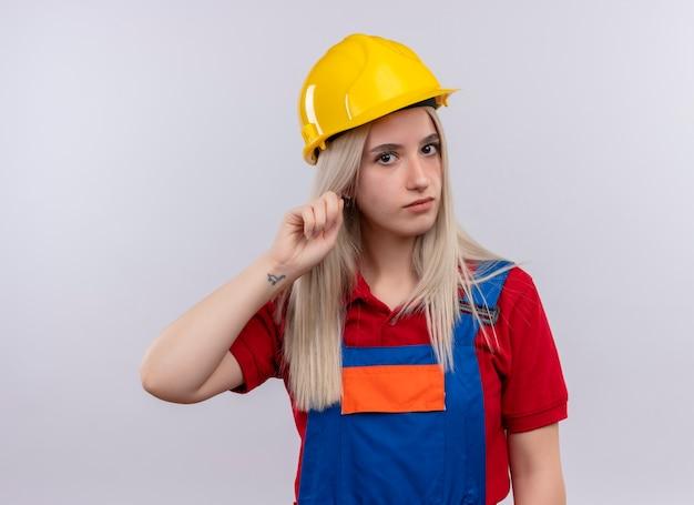 Jeune fille blonde ingénieur constructeur en uniforme mettant le doigt sur l'oreille à la recherche sur le mur blanc isolé