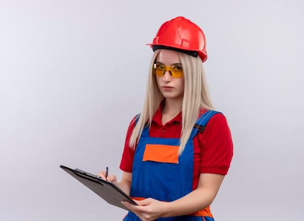 Jeune fille blonde ingénieur constructeur en uniforme portant des lunettes de sécurité écrit sur le presse-papiers sur mur blanc isolé