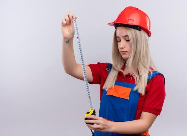 Jeune fille blonde ingénieur constructeur en uniforme tenant mètre ruban et en le regardant sur un mur blanc isolé avec copie espace