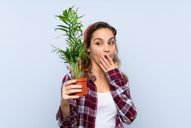 Jeune fille blonde jardinier tenant une plante avec une expression faciale surprise et choquée