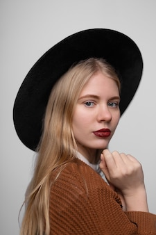 Jeune fille blonde jolie souriante heureuse avec chapeau à larges bords et les lèvres peintes avec rouge à lèvres rouge vif, regardant la caméra