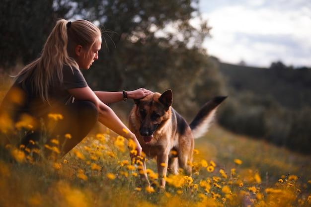 Jeune fille blonde jouant avec un chien de berger allemand dans un champ de fleurs jaunes