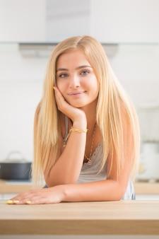 Jeune fille blonde joyeuse dans la cuisine de la maison. elle pense à ce qui va cuisiner aujourd'hui.