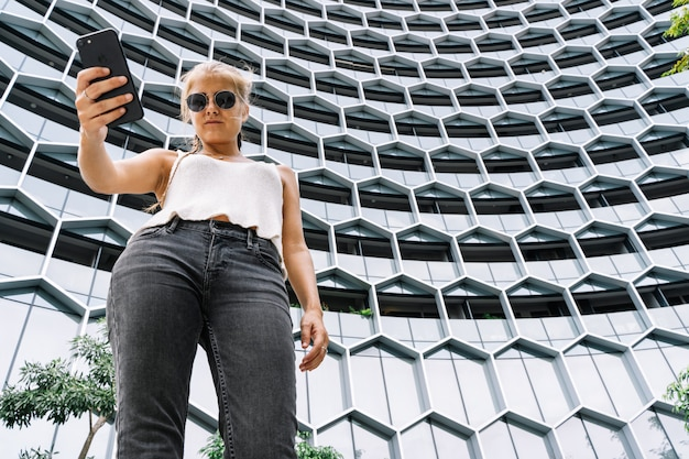 Jeune fille blonde avec des lunettes de soleil debout devant un bâtiment moderne à l'aide d'un mobile