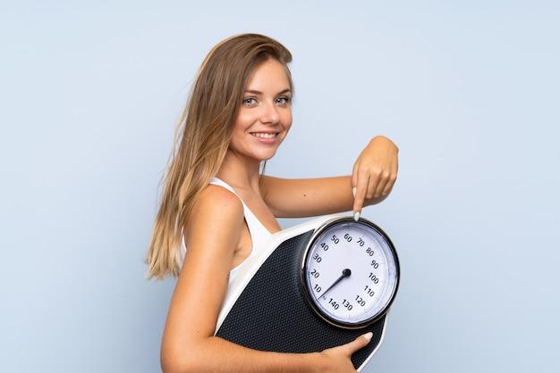Jeune fille blonde avec une machine de pesage sur blanc bleu isolé