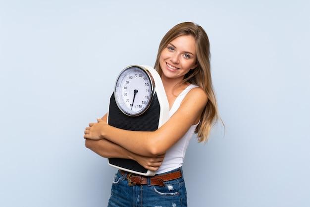 Jeune fille blonde avec une machine de pesage sur fond blanc bleu isolé