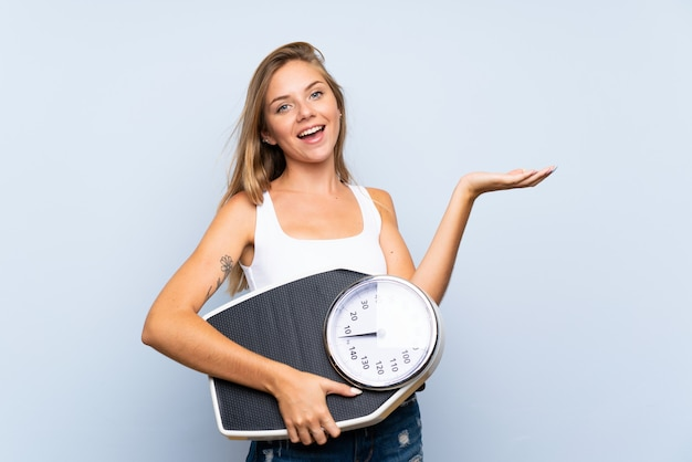 Jeune fille blonde avec une machine de pesage sur un mur blanc bleu isolé