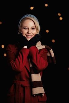 Jeune fille blonde en manteau rouge et écharpe sur le mur avec des guirlandes