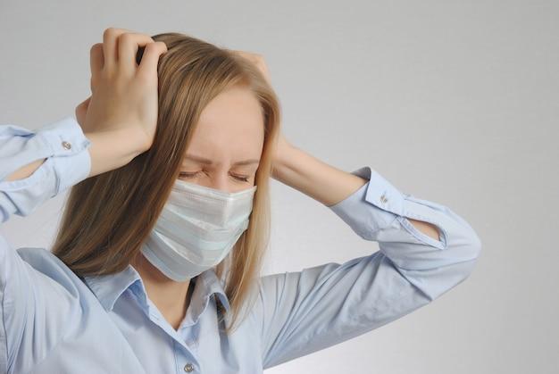 Jeune fille blonde avec des maux de tête en masque médical