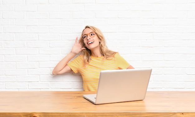 Jeune fille blonde à l'ordinateur portable essayant d'écouter un secret
