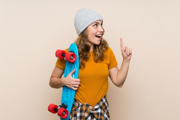 Jeune fille blonde de patineur ayant l'intention de réaliser la solution tout en levant un doigt