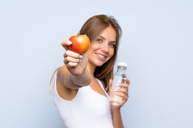 Jeune fille blonde avec une pomme et une bouteille d'eau