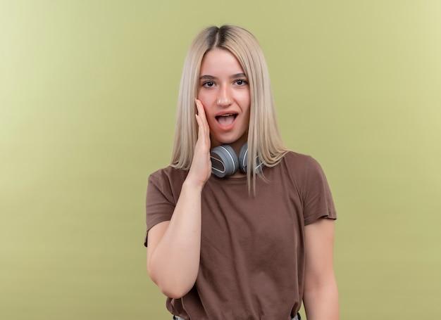 Jeune fille blonde portant des écouteurs sur mur vert isolé