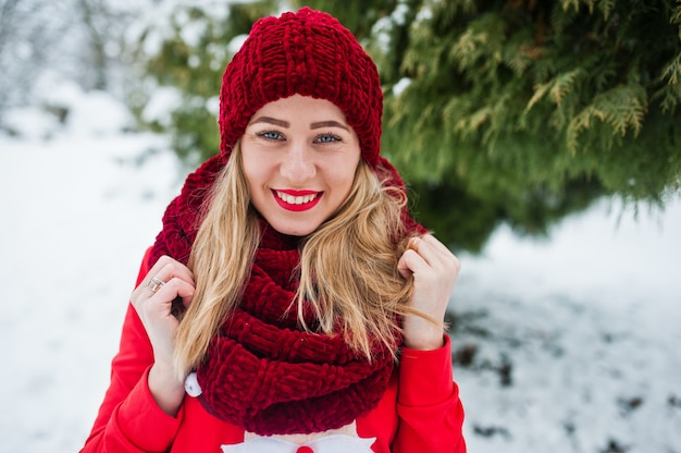 Jeune fille blonde en pull rouge écharpe, bonnet et santas posant au parc le jour de l'hiver.