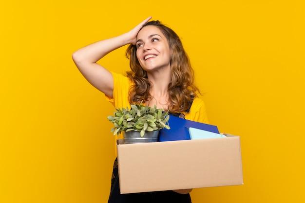 Une jeune fille blonde qui bouge tout en ramassant une boîte pleine de choses a réalisé quelque chose et a l'intention de la solution