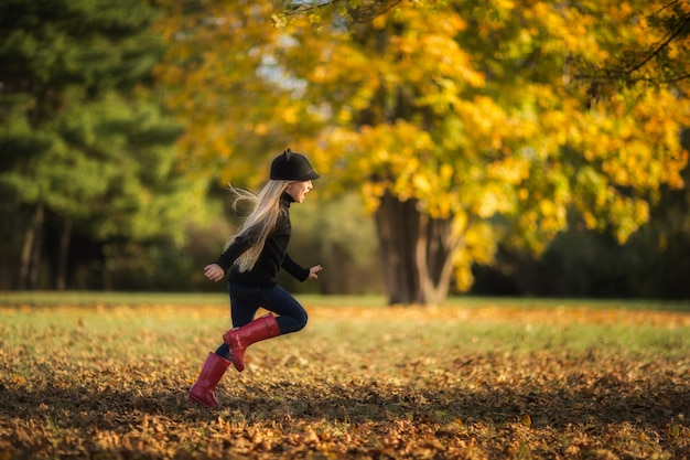 Jeune fille blonde qui court au parc automne.
