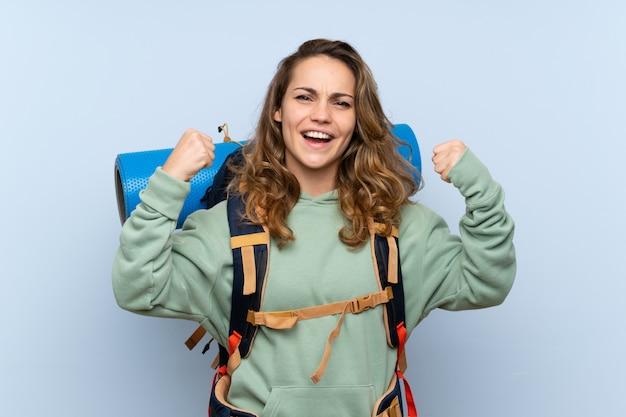 Jeune fille blonde randonneur sur mur bleu isolé, célébrant une victoire
