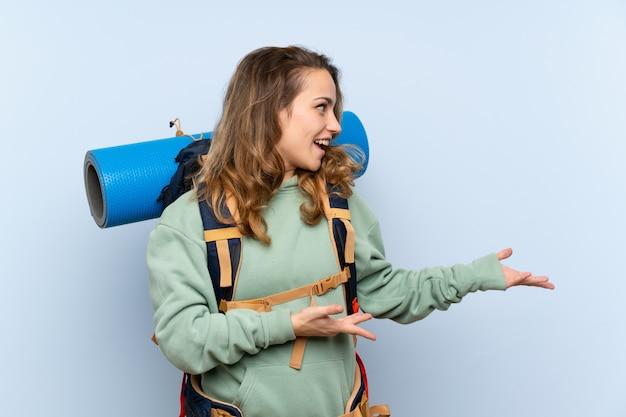Jeune fille blonde randonneur sur mur bleu isolé avec une expression faciale surprise
