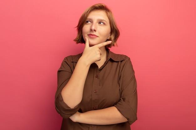 Jeune fille blonde réfléchie touchant le menton regardant le côté isolé sur fond rose avec espace de copie