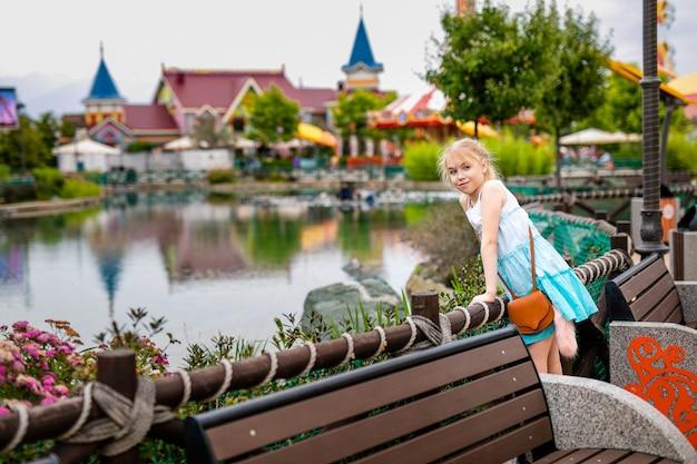 Jeune fille blonde en robe blanche et bleue dans le parc d'été de divertissements