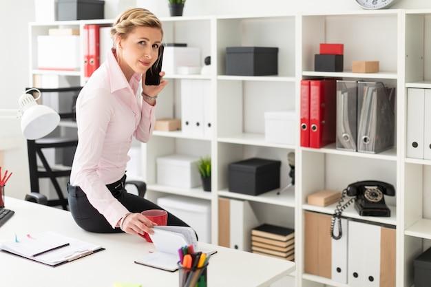 Une jeune fille blonde s'assied sur le bureau du bureau, parle au téléphone et feuillette le bloc-notes.