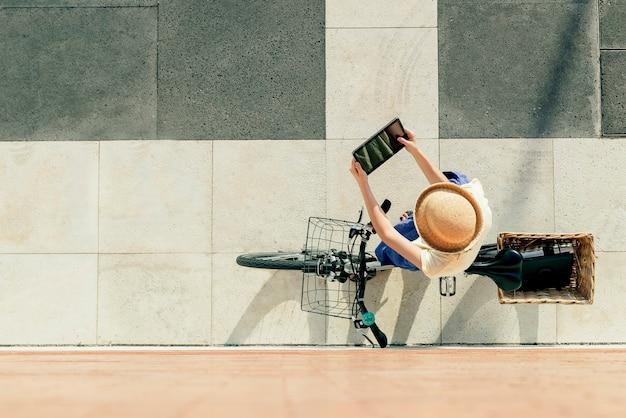 Jeune fille blonde sexy est assise près du vélo avec une jupe bleue et un chapeau. elle a une tablette.