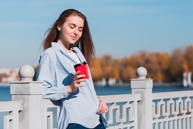 Jeune fille blonde souriante tenant une tasse de café