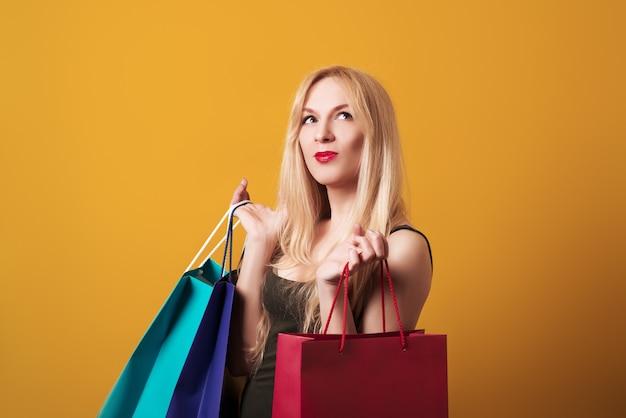 Jeune fille blonde tenant des sacs isolés