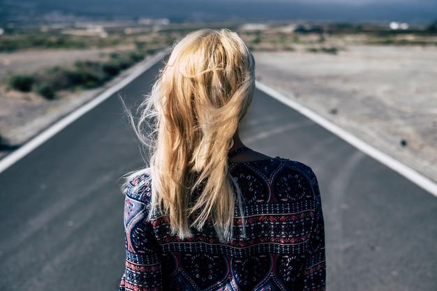 Jeune fille blonde vue de l'arrière à pied sur une longue route droite à la campagne. décisions et futur concept pour les personnes du millénaire à la recherche d'un emploi ou d'un chemin vers le bonheur - liberté et peur
