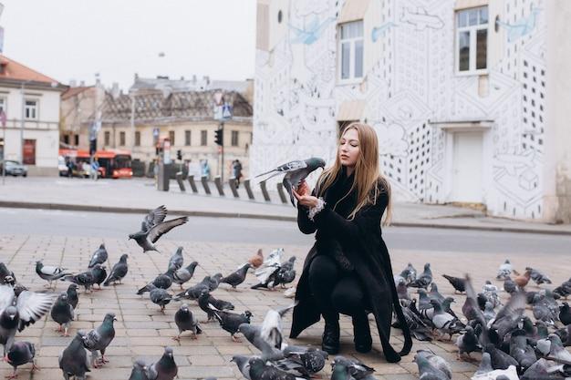 Jeune fille blondie positive dans la ville nourrir un troupeau de pigeons
