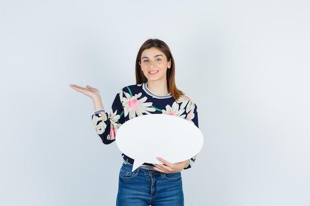 Jeune fille en blouse florale, jeans écartant la paume et l'air heureux, vue de face.