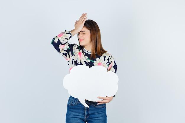 Jeune fille en blouse florale, jeans avec la main sur la tête et l'air contrarié, vue de face.