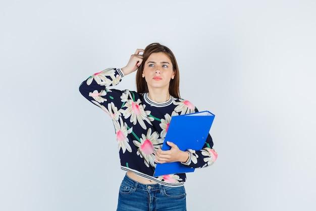 Jeune fille en blouse florale, jeans avec la main sur la tête et à la nostalgie, vue de face.