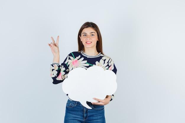 Jeune fille en blouse florale, jeans montrant le signe v et l'air heureux, vue de face.