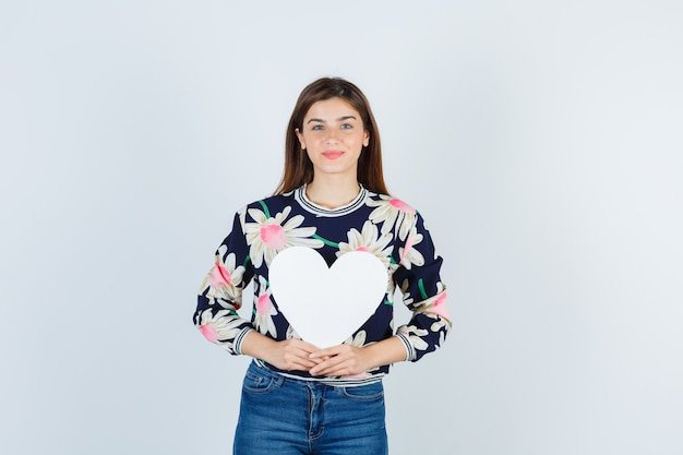 Jeune fille en blouse florale, jeans tenant une affiche en papier et l'air satisfait, vue de face.