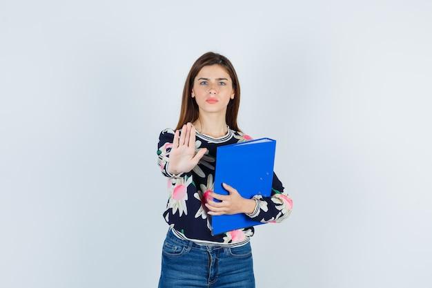 Jeune fille en blouse florale, jeans tenant un dossier, montrant un geste d'arrêt et l'air perplexe, vue de face.