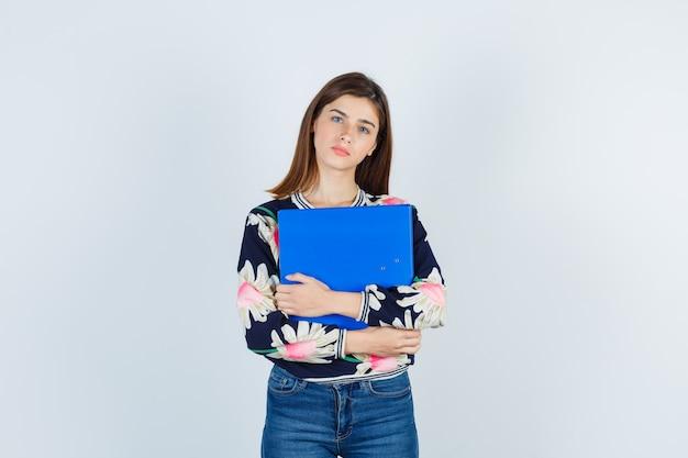 Jeune fille en blouse florale, jeans tenant le dossier et à la nostalgie, vue de face.