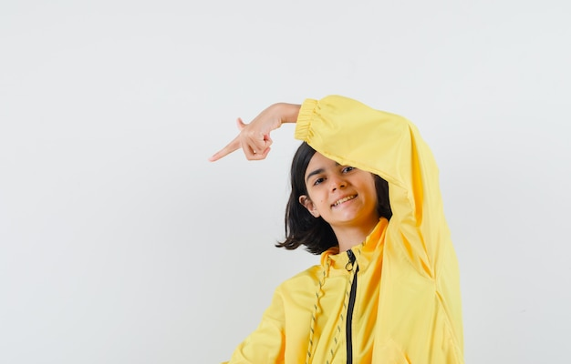 Jeune fille en blouson aviateur jaune et jupe rose pointant dans le coin inférieur gauche avec index et à heureux