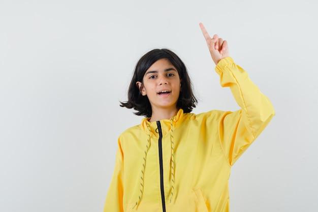 Jeune fille en blouson aviateur jaune levant l'index en geste eureka et à heureux
