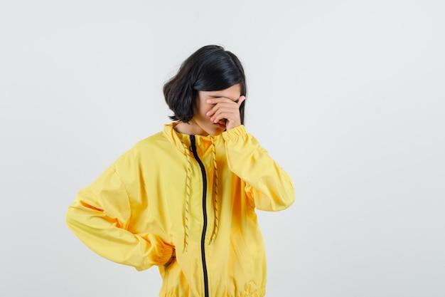 Jeune fille en blouson bomber jaune couvrant une partie du visage avec la main, mettant une autre main sur la taille et à regret