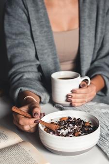 Une jeune fille boit du café le matin, mange un petit-déjeuner sain et lit un livre.
