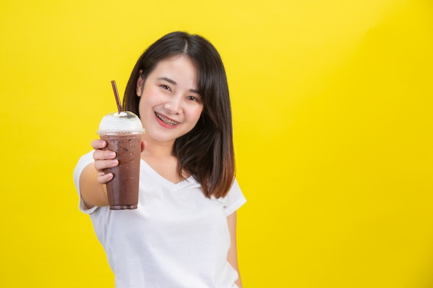 La jeune fille boit de l'eau froide dans du cacao dans un verre en plastique transparent sur un fond jaune.