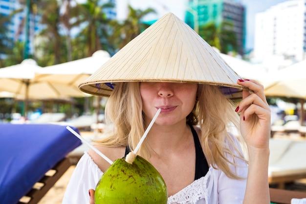 Jeune fille boit d'une noix de coco dans un chapeau conique asiatique traditionnel assis sur la plage